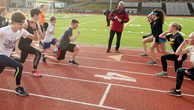 South Kitsap track and field coach Ed Santos talks to his team during warmups at a recent practice. Santos returned to coaching after spending 11 years as South Kitsap's athletic director.