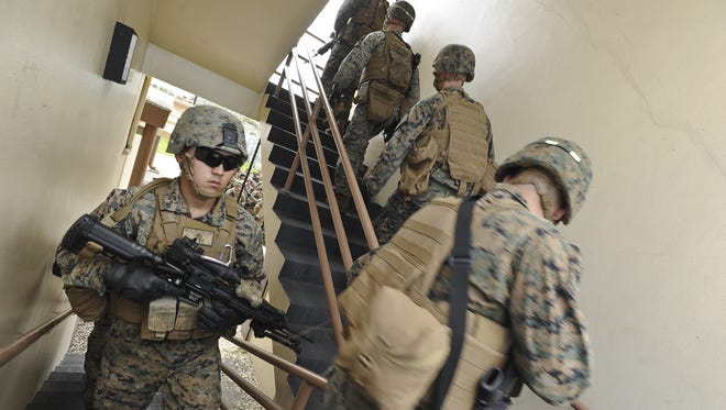 Members of the 3rd Battalion 6th Marines ascend the stairs of the Explosive Ordnance Disposal Mobile Unit Five rappelling tower during a fast-rope training exercise at the Naval Base Guam in March 2013. Marines from Okinawa are scheduled to begin a training exercise on Guam beginning Aug. 10.
