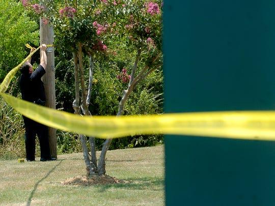 A Shreveport Police Officer puts up crime tape.