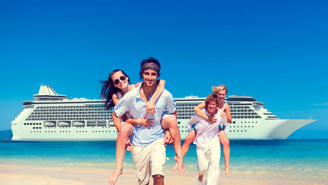 Two couples walk on the beach by a cruise ship.