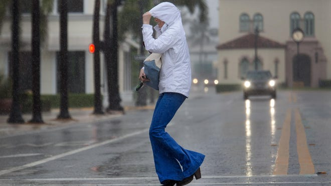 A woman dashes across South County Road at Worth Avenue in the pouring rain in Palm Beach, March 30, 2016.