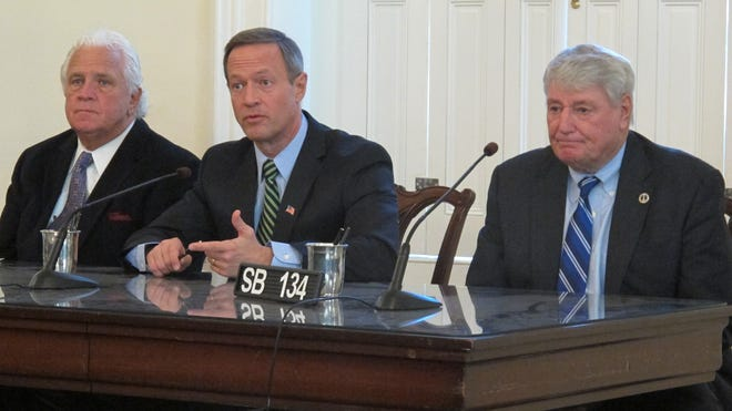 Maryland Gov. Martin O'Malley, center,  signs an emergency bill  Jan. 30 in Annapolis, Md., to enable people who could not enroll in a health insurance plan on the state's health exchange website to get retroactive coverage.