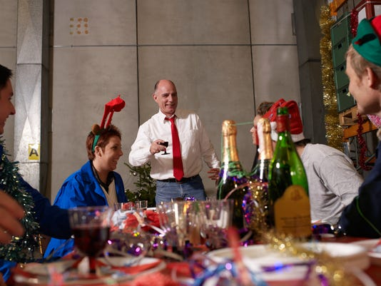 Group of workers celebrating at charismas table in warehouse