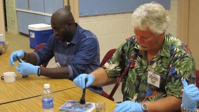 Members of the Fort Myers   Citizen Police Academy dust for fingerprints.