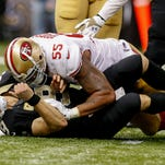 New Orleans Saints quarterback Drew Brees (9) is tackled by San Francisco 49ers outside linebacker Ahmad Brooks (55) during the fourth quarter at Mercedes-Benz Superdome. The 49ers won 27-24 in overtime.
