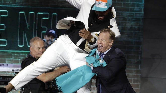 Clemson defensive tackle Christian Wilkins crashes into NFL Commissioner Roger Goodell last year in a scene that won't be repeated when this year's draft is held remotely.