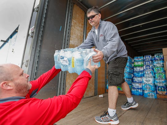 Chris Porter,right, takes in bottles of water at the