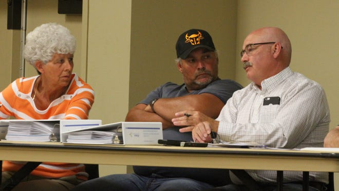 Poweshiek County Zoning Board of Adjustment members, from left, Coleen Van Dyke, Roger Cheney and temporary chair Mark Kennett discuss the two wind turbine proposals by Tradewind Energy prior to a vote to allow the turbine projects to proceed.