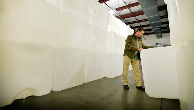 Chad Odom, CEO of Encore Container, inspects a plastic container in the company's vast warehouse on Oct. 27, 2015.