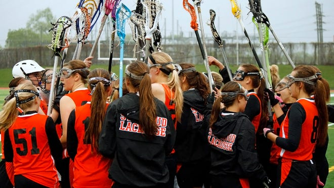 The St. Cloud Area girls lacrosse team huddles before the start of the second half of their game against Wayzata on Monday night.