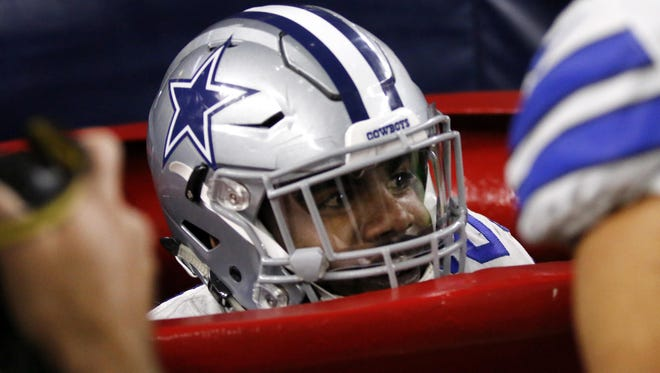 Dallas running back Ezekiel Elliott peeks out of a large Salvation Army kettle after jumping into it to celebrate a touchdown against the Tampa Bay Buccaneers on Dec. 18 in Arlington, Texas.