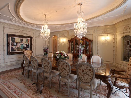 Dining room with ornate plaster work. Country French Normandy-style Estate in a private gated community in Oakland Township. Custom-designed estate built in 2007 with 14,000 square-feet of luxury on 4 acres. Listed for $7.5 million. This estate has many custom details and old world craftsmanship.There is Florida room with floor to ceiling windows with views to the expansive grounds, lots of natural stone, Pecan wood floors, Lower level has radiant heat a carriage apartment and 6 car garage to name a few amenities.