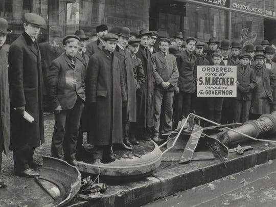 A group of men stands over a street clock that was demolished by orders of Mayor Sherburn Becker in 1906.