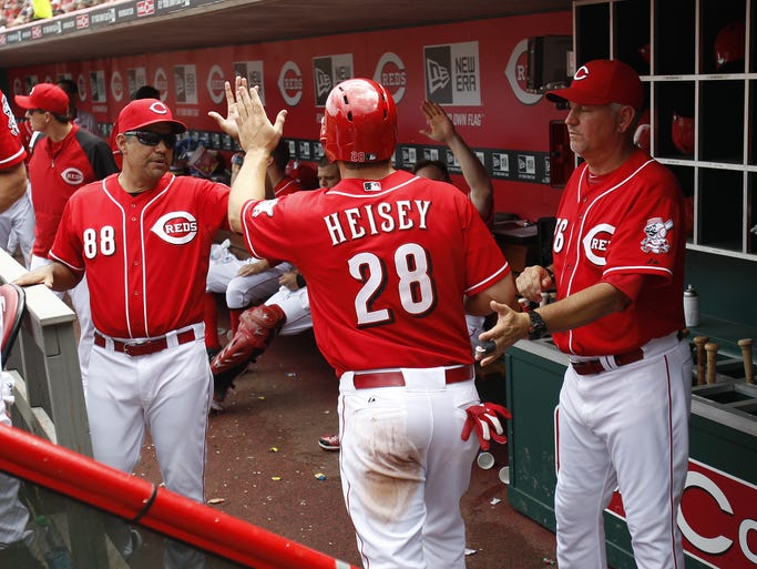 Cincinnati Reds left fielder Chris Heisey (28) is congratulated after scoring on a hit by shortstop Ramon Santiago (7) against the Chicago Cubs during the sixth inning of their game played at Great American Ball Park.