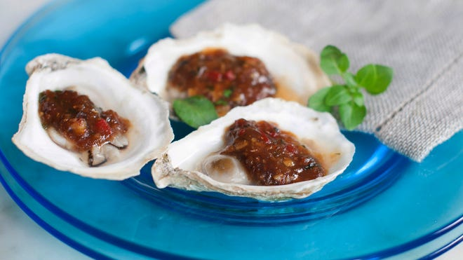 Grilled oysters served with miso black beans and chili garlic make a delicious start to the summer cookout season.