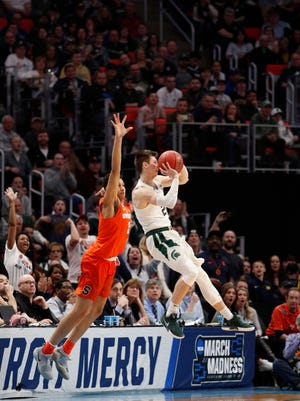 Michigan State Spartans guard Matt McQuaid (20) shoots a 3-point buzzer beater in the first half against the Syracuse Orange  in the second round of the 2018 NCAA Tournament at Little Caesars Arena.