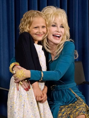 Dolly Parton hugs Alyvia Lind during a press conference in 2015.