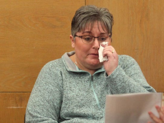 Leanne Fluckey cries as a prosecutor shows her a picture