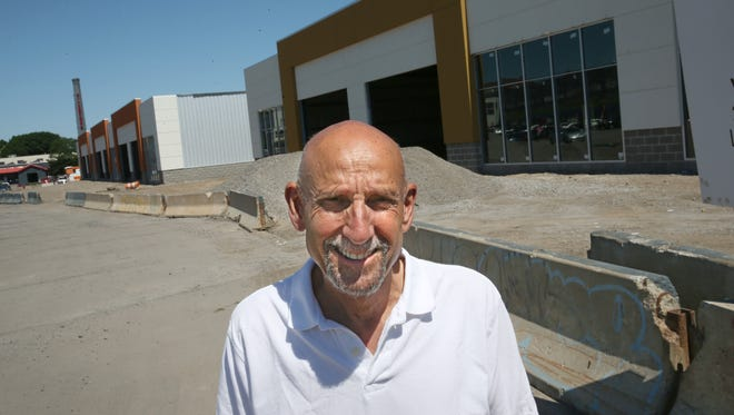 Gary Stern stands outside two of the three new buildings currently under construction at Village Gate in a 2016 file photo.