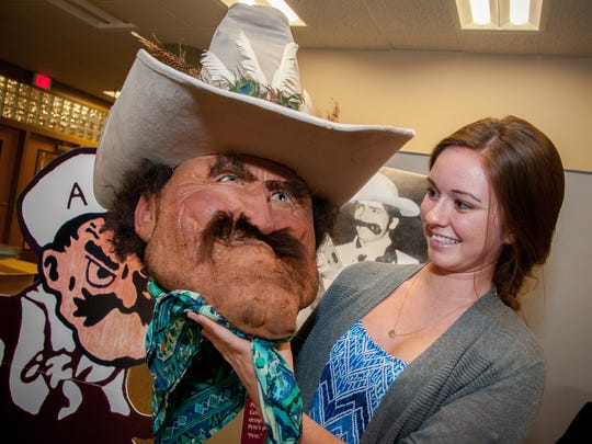 Zuhl Library student aide Adelina Perraglio holds up a NMSU Pistol Pete mascot head shown as part of an exhibit of Pete throughout the years. On the left you can see a cut-out of the  'classic Pete' design and to the right a photograph of Pistol as he was portrayed in the early 1970's.