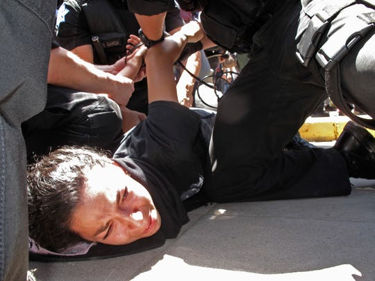 Police officers take a woman into custody after a rally