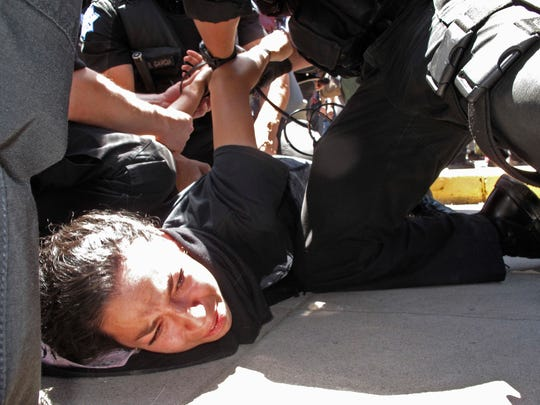 Police officers take a woman into custody after a rally by Republican presidential candidate Donald Trump in Fresno, Calif., Friday, May 27, 2016. Police officers told hundreds of protesters to clear the streets in downtown Fresno following the Trump rally. Officers dressed in riot gear arrested two people on suspicion of unlawfully assembly after they refused orders.