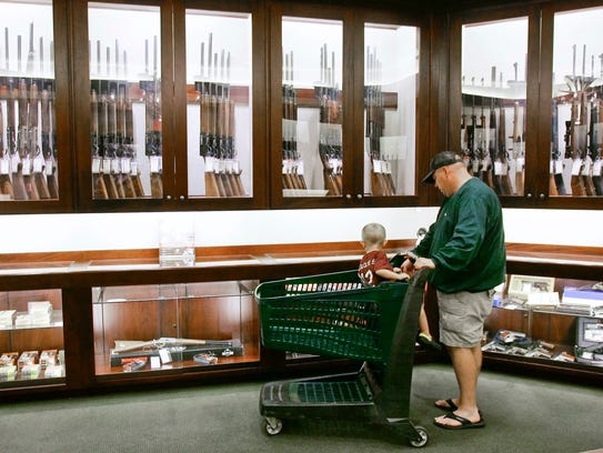 An unidentified father and son look at firearms displayed