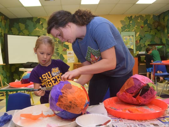 Marissa Sonnier (right) helps Emily Daigre make a papier-mache birdhouse Wednesday during a summer camp held at the T.R.E.E. House Children's Museum.
