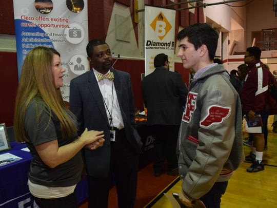 Cleco human resources representatives Traci O'Brien (left) and Basil Smith talk with Austin Etier, a junior at Pineville High School, during the school's college and career fair Thursday.