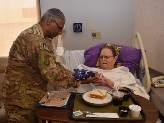 Air Force Master Sgt. Alvin Jefferies (left) presents Navy veteran Edward Richardson a flag flown during combat missions. Jefferies drove Thursday from Alabama to Rapides Regional Medical Center where Richardson is a patient with stage 4 bone cancer.
