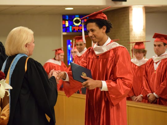 St. Joseph High School Principal Lynn Domenico congratulates Erick Colon, 18, of Sicklerville during the graduation ceremony.