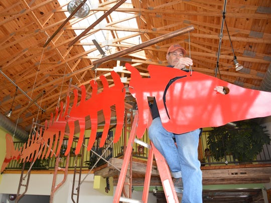 Ron Harris removes his 20-foot steel sturgeon hanging from the ceiling of The Flying Pig.
