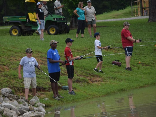 Cade Bordelon (left), Cameron Nicholas and Austin Ivey and fellow campers fish Tuesday in a pond at the Woodworth Education Center. The Louisiana Department of Wildlife and Fisheries is hosting its Summer Fishing Camp this week teaching children about bait and tackle, fish identification, fish cleaning, bowfishing and species-specific rigging for panfish, catfish and bass.