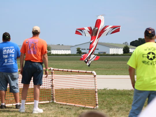 A radio-controlled model airplane performs a 'tail touch' while prop flying at Wings and Warbirds Over Port Clinton.