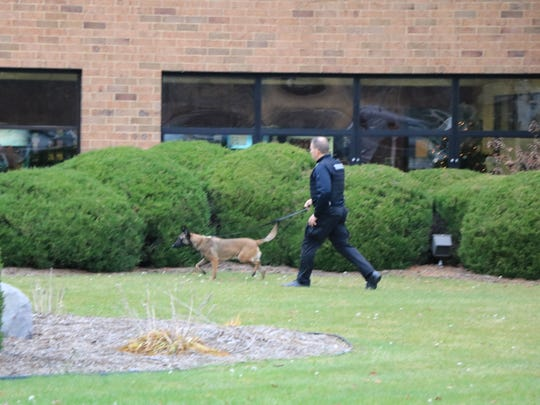 An officer and a bomb-sniffing K-9 investigate after a bomb threat at Step 2 in Perrysville on Saturday.