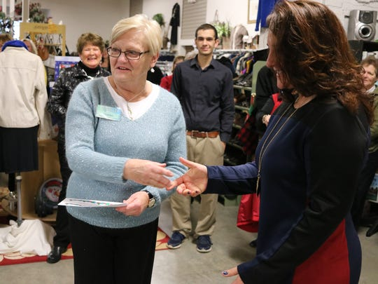 Sharon McCullough, left, of the Portage Resale Center, hands a charitable donation to Carrie Sanchez, principal of Port Clinton Middle School.