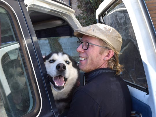 "Georgie Cutright (right) gets one of his two Siberian Huskies out of his Chevy van on Wednesday, February 15. Cutright says he will attempt to be the first person to travel across the country ""only on dog power."""