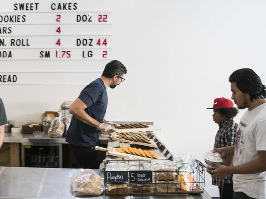 Owner Sean Huntington (center) sells cookies at Sweet Cakes Cafe on Main Street in Mesa.