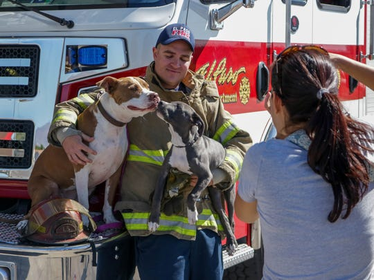 El Paso Firefighter Ryan Mielke holds Reina and Suul while volunteer photographer Kendra Porta takes a photo for the 2018 calendar.