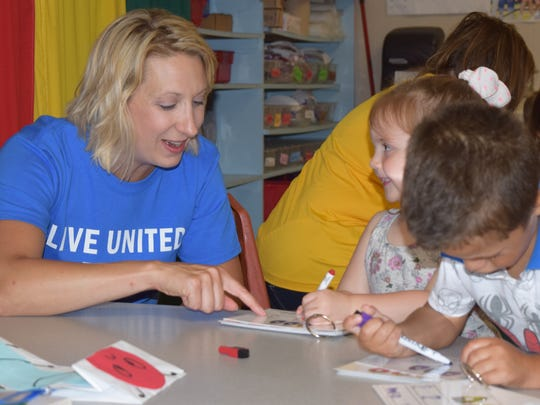 A United Way of the Southern Tier volunteer works with children.