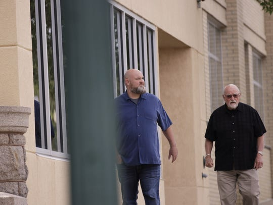 Tim Burns (left) walks to his appearance in federal