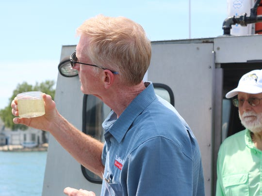 Larry Fletcher, president of Lake Erie Shores and Islands, checks out a water sample from the lake.