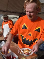 J.J. Haring prepares a signature Door County Caramel Apple using sliced apples, caramel, whipped topping, candy sprinkles, nuts and topped with a cherry during last year's Pumpkin Patch.