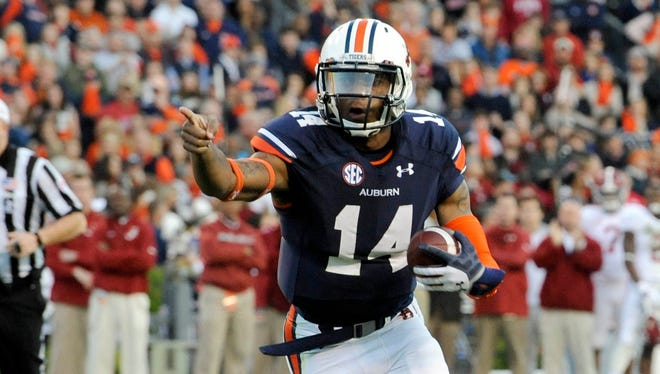 Auburn quarterback Nick Marshall (14) points as he carries the ball in the second quarter Saturday at Jordan-Hare Stadium. The Tigers snapped Alabama's winning streak with a 100-yard return of a missed field goal with no time remaining.