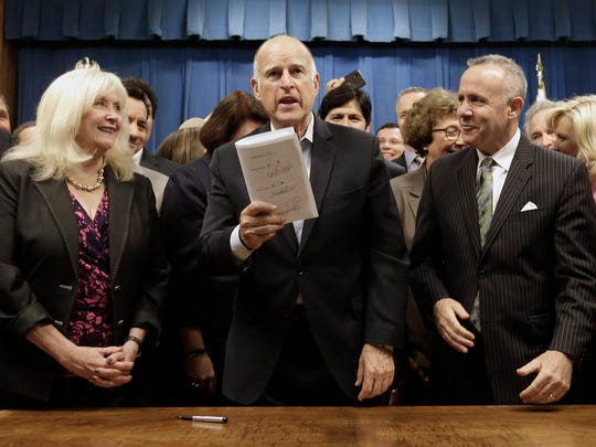 Gov. Jerry Brown, flanked by Assembly Minority Leader