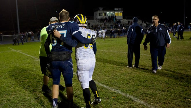 Richmond's Zachary Roberts consoles Algonac's Mason Ruhlman after a football game Friday, October 16, 2015 at Richmond High School.