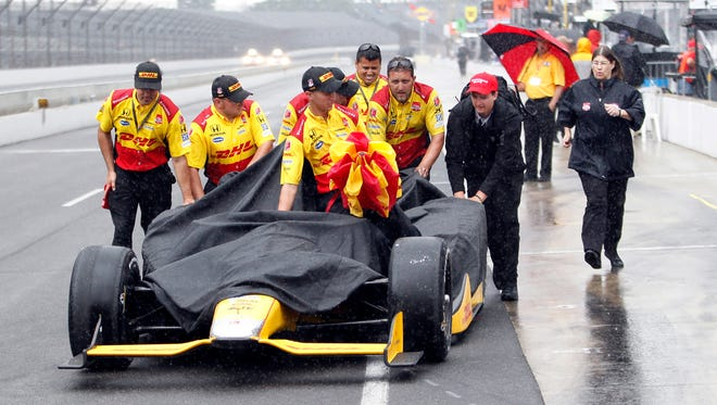 The crew of Ryan Hunter-Reay pushes the car back to the garage area after rain halted action on the first day of qualifications for the Indianapolis 500 auto race at Indianapolis Motor Speedway in Indianapolis, Saturday.