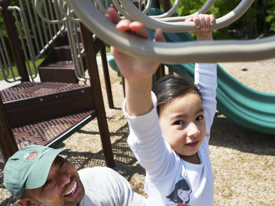 Mel Cabili of Webster smiles at his daughter, Ivy, 3, as she moves across the monkey bars at Abraham Lincoln Park.