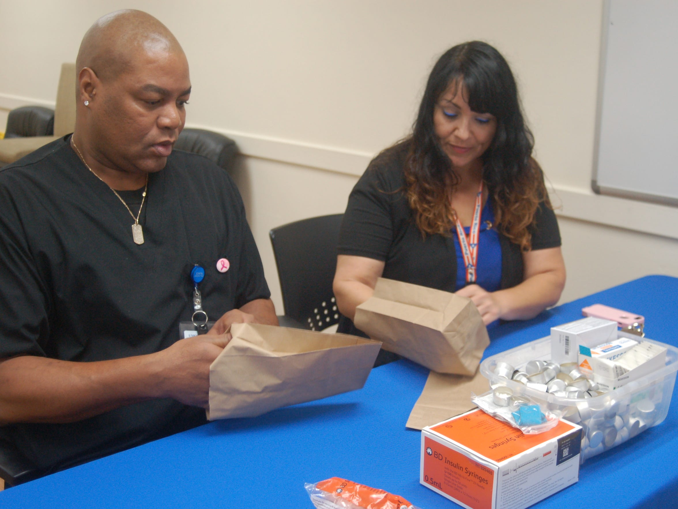 Gina Allende, health promotions manager at UMOS, and outreach worker Naronne Cole Sr. package syringes, cookers, alcohol pads and cotton pellets for clients of the UMOS Safe Exchange Program on Milwaukee's south side.