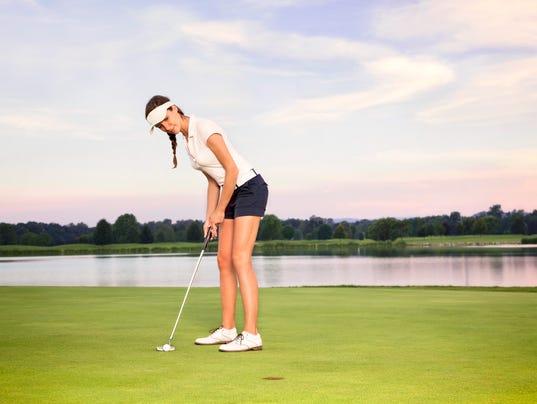 Girl golfer putting.